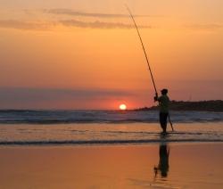 Man fishing at sunset in Mehdya beach, Morocco